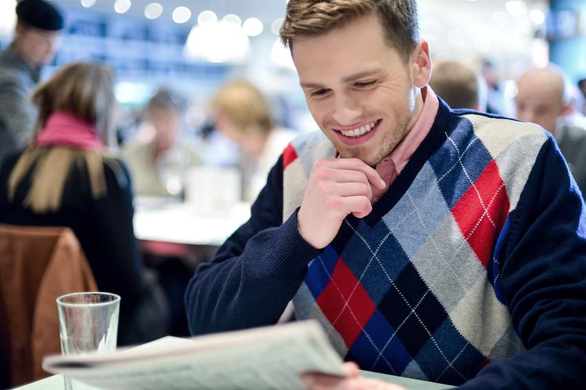 Stylish man reading newspaper at cafe